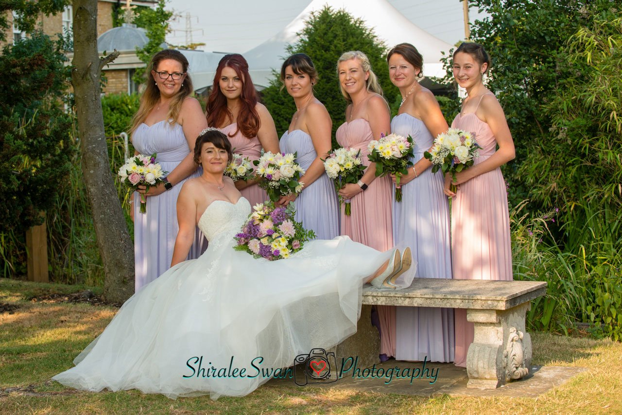 The Bride with her beautiful bridesmaids on one of the benched in the gardens at Friern Manor