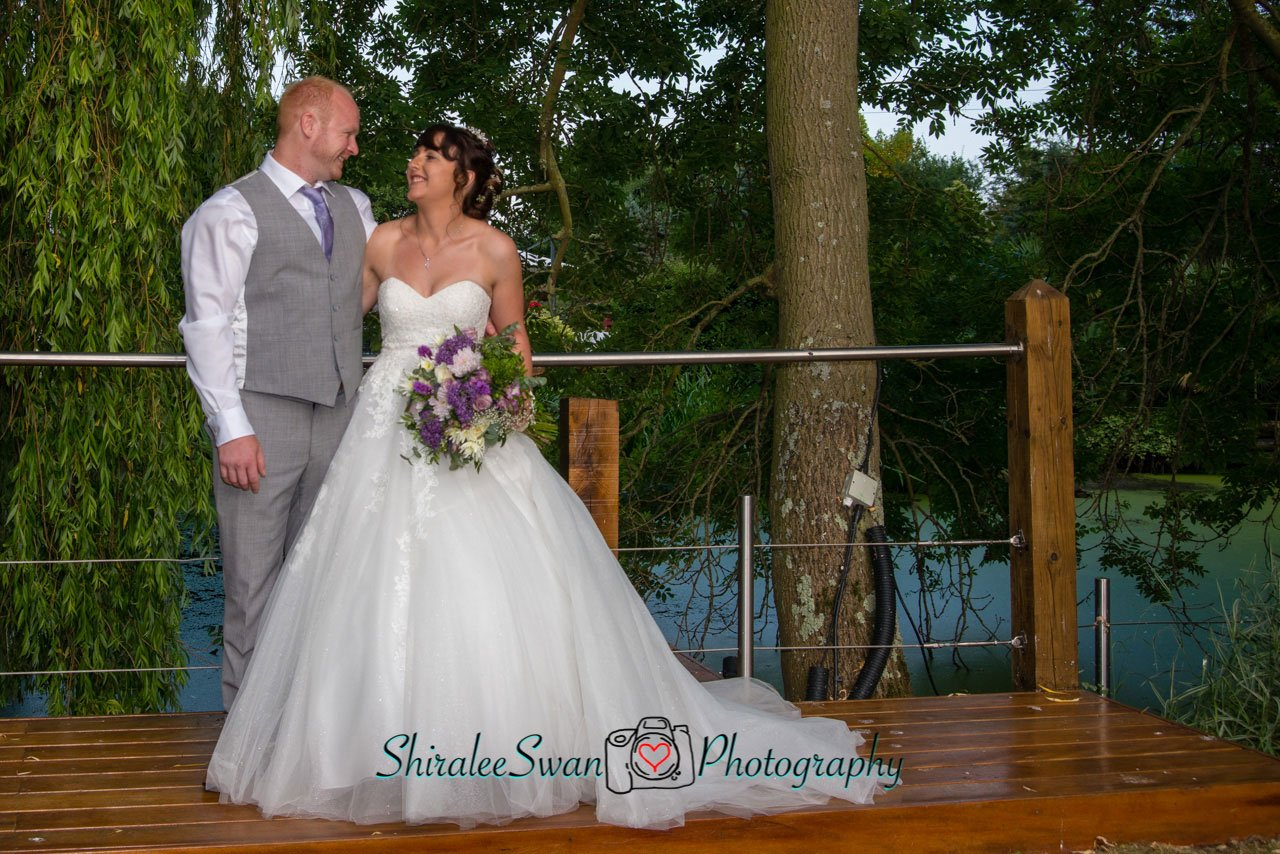 bride and groom with Friern Manor lake in the background