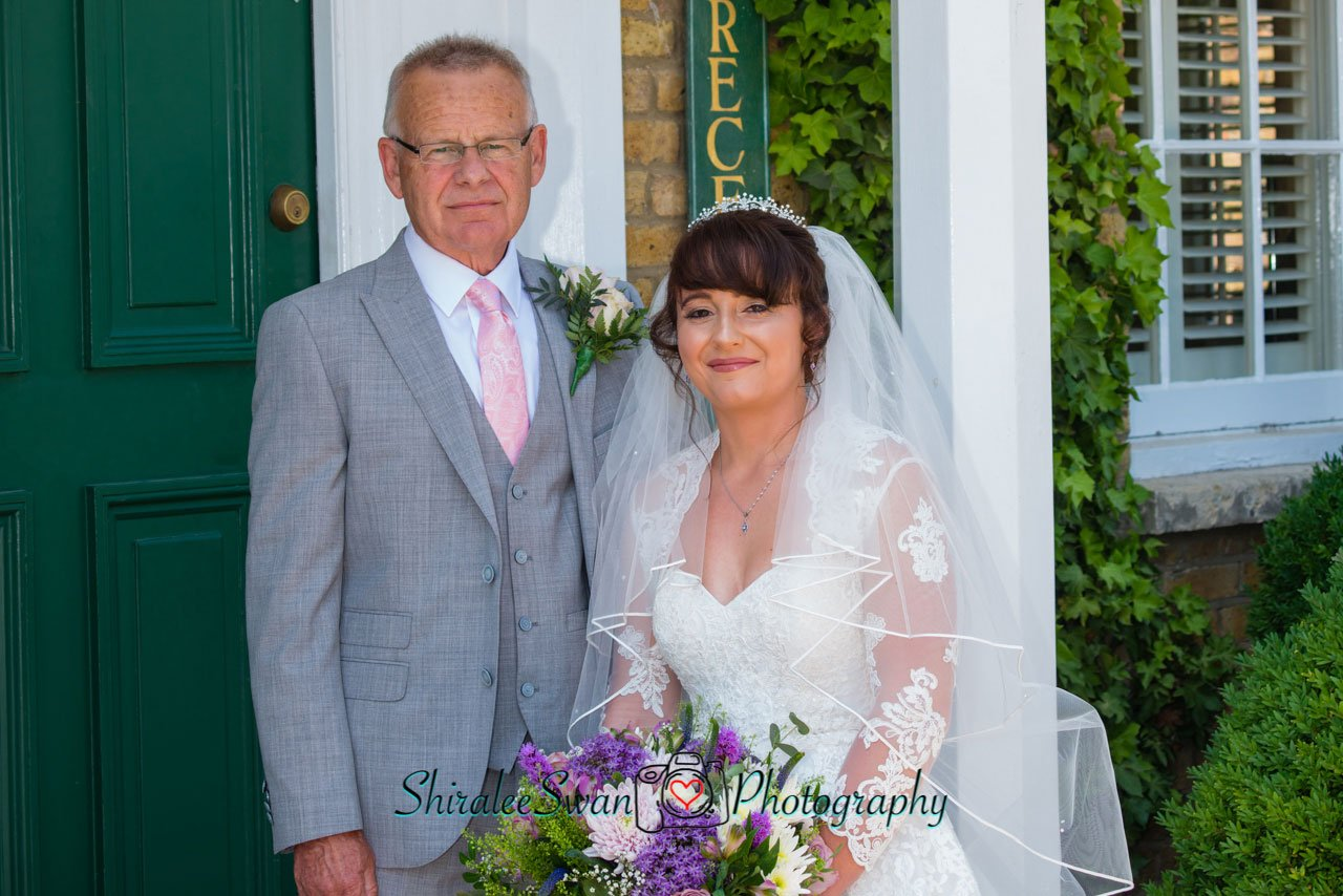 the bride with her dad standing at the front door at at Friern Manor