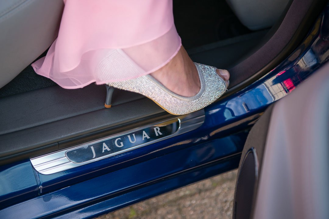The bride stepping from a Jaguar car