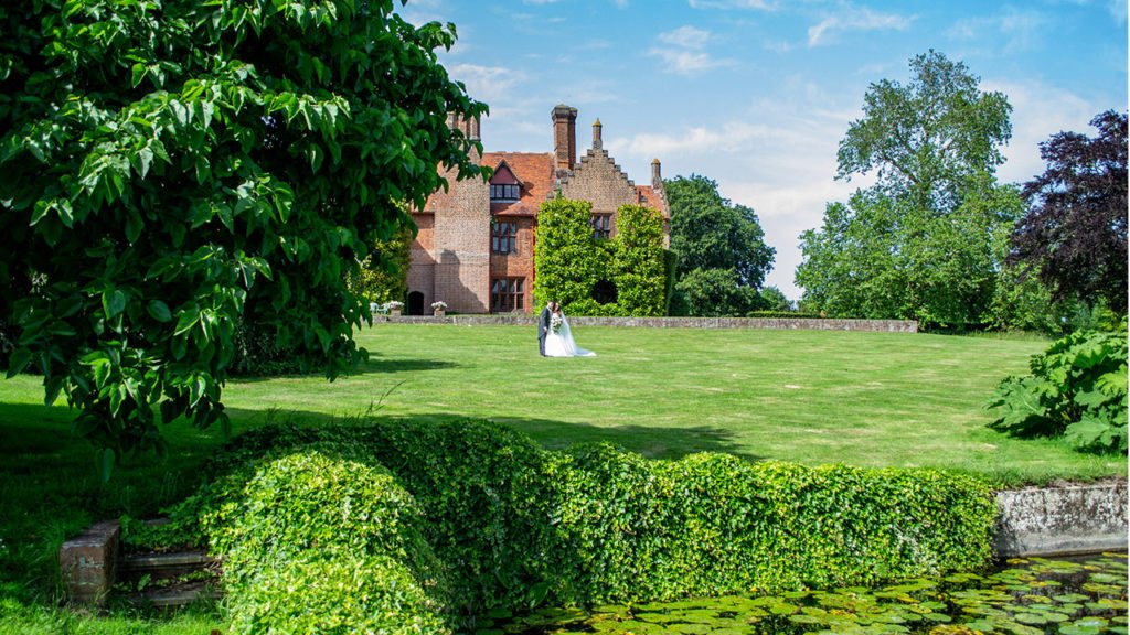 The Bride and Groom stand in the middle of a large lawn in front of Ingatestone Hall. In the gardens, there is a large pond covered with water lilies there are large trees in the garden too.