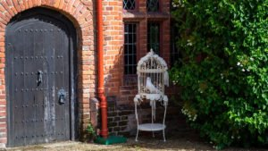 In a corner of the courtyard of Ingatestone Hall, two white doves are placed in the shade in their ornate cage to keep them coolIn a corner of the court yard of Ingatestone Hall